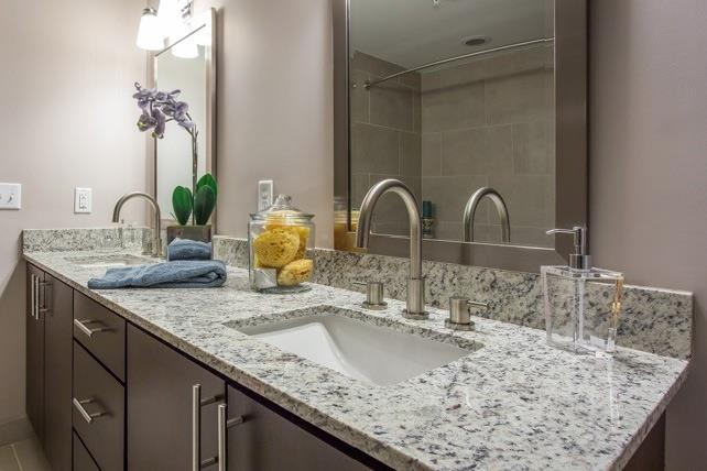 Granite countertop and contemporary wood cabinets for apartment bathroom